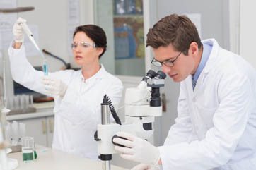 Scientists working with microscope and test tube in laboratory
